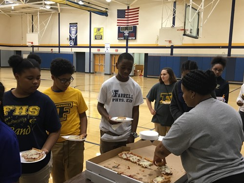 Farrell middle school students in line to get pizza during a party rewarding them for making the honor roll