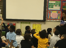 Elementary school students gathered around listening to and discussing a book during the National African American Read-In